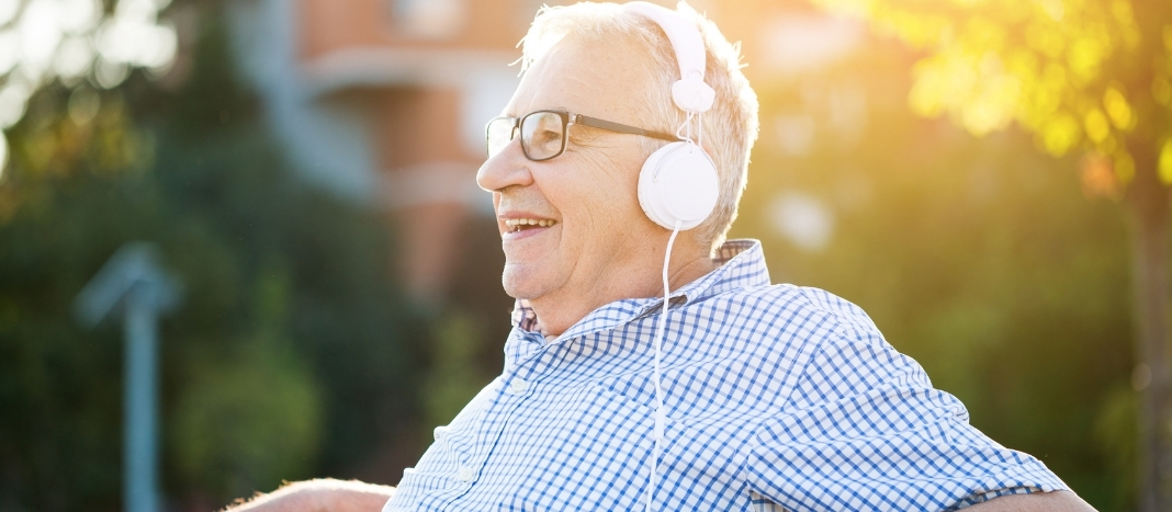 A senior man wearing headphones while sitting on a bench