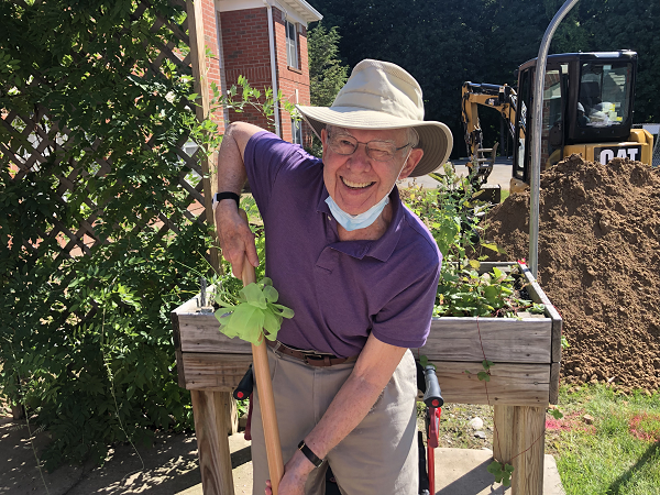 Resident and member of The Highlands Resident Council smiling with shovel, ready to dig