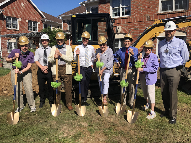 Members of The Highlands Resident Council and Executive Director Lloyd Theiss standing in a line holding shovels at the Memory Care Groundbreaking Ceremony