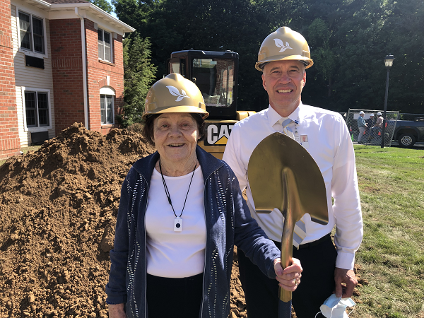 Resident and member of The Highlands Resident Council standing with shovel along with Executive Director Lloyd Theiss